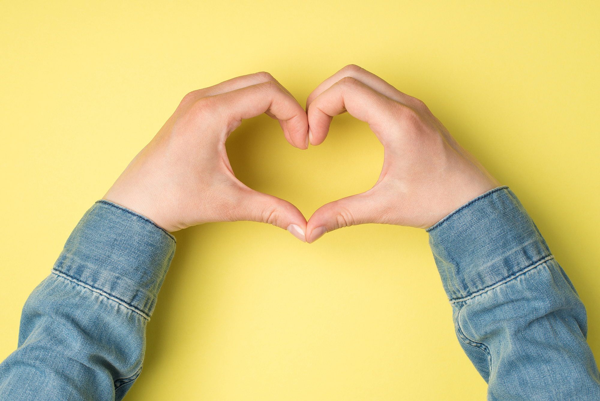 First person top view photo of woman's hands showing heart sign with fingers on isolated yellow background with copyspace